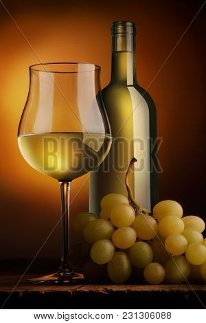 Goblet Of White Wine Bottle And Bunch Of Grapes