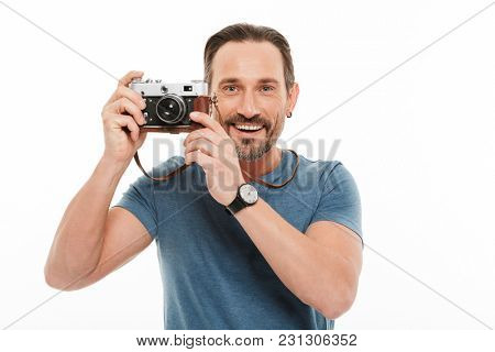 Portrait of a cheerful mature man dressed in t-shirt holding photo camera isolated over white background