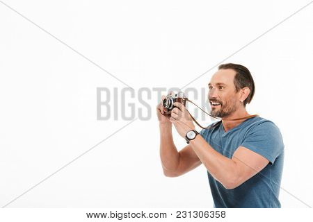 Portrait of a cheerful mature man dressed in t-shirt holding photo camera and looking away at copy space isolated over white background