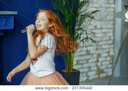 The Child Sings The Song In The Microphone. Very Long Hair. The Concept Is Childhood, Lifestyle, Mus