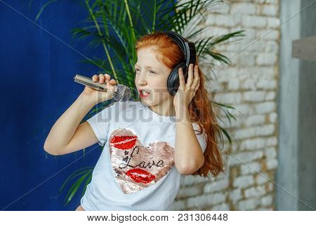 A Teen Girl Sing A Song In A Microphone. The Concept Is Childhood, Lifestyle, Music, Singing, Listen