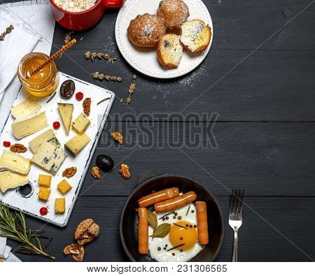 Fried Chicken Egg And Sausages In A Black Crockery Cast-iron Frying Pan, Pieces Of Brie Cheese, Roqu