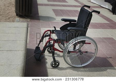 Empty Wheelchair On A Beach Near Beach