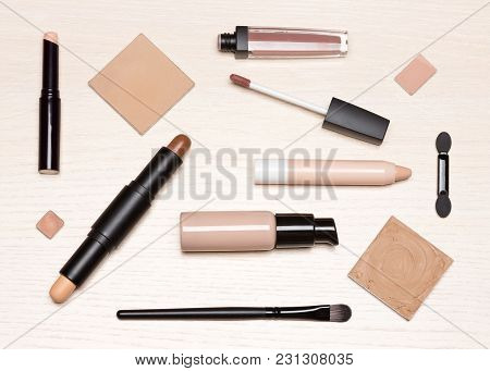 Basic Makeup Products: Primer, Concealer, Liquid Foundation, Cosmetic Face Powder On Light Wood Tabl