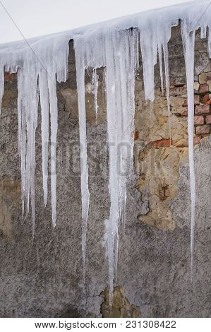 Huge Dangerous Icicle Formation On The Rooftop. Hazardous Ice Melting Hanging From The Roof Of An Ol