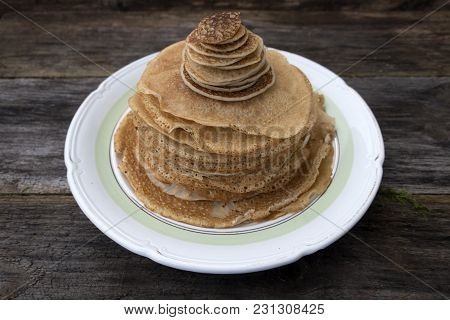 Large And Small Pancakes Located On An Old Wooden Table.