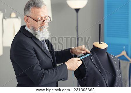 Senior tailor taking measurements of mannequin in atelier poster
