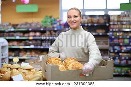 Young woman holding crate with bakery products in shop. Small business owner