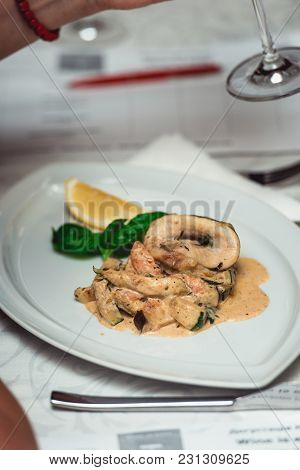 Portion Of Delicious Fish Fillet In Sauce At The Restaurant. Small Portion On A White Plate. Food An