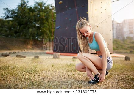 Rock Climber Woman Putting On Climbing Shoes While Sitting On Grass. Pretty Girl Prepares For Workou