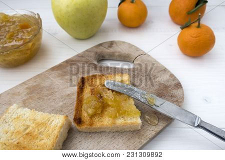 A Sandwich With Fruit Jam And A Knife That Spread The Jam On Fried Bread.