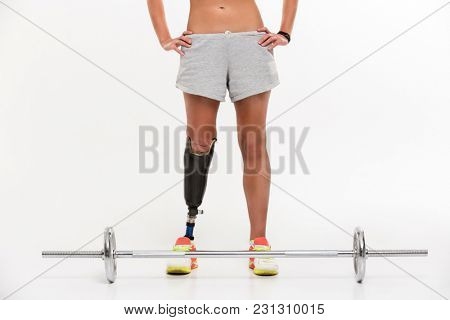 Cropped photo of young disabled sports woman with prosthesis isolated over white background make exercise with barbell.
