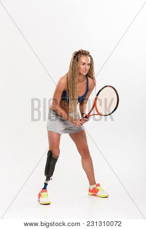 Full length portrait of a confident young disabled sportswoman with leg prosthesis doing exercises with tennis racket isolated over white background