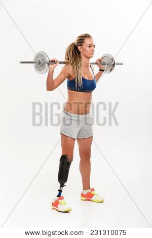 Image of young disabled sports woman with prosthesis isolated over white background. Looking aside make exercise with barbell.
