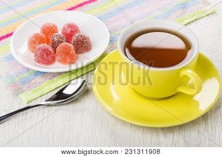 Red Marmalade In Saucer On Napkin, Teaspoon, Cup Of Tea On Wooden Table