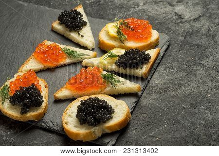 Red Salmon Roe And Black Stugeon Caviar On The Black Stone Board On A Black Table, Top View With Cop