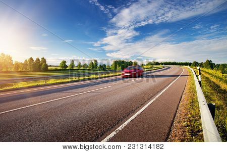 Asphalt Road In Countryside With A Car. Vehicle Moving On Beautiful Sunny Evening