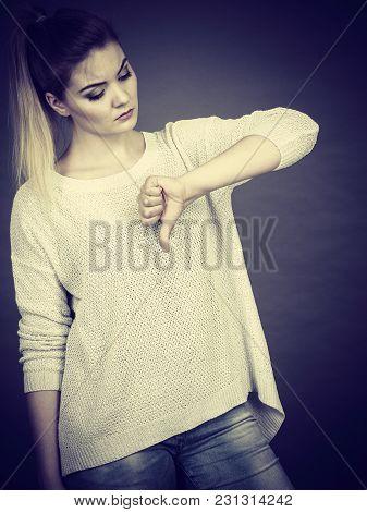 Unlike, Dislike, Failure Gestures Concept. Sad Woman Showing Thumb Down Gesture, Studio Shot Grey Ba