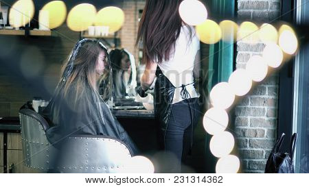 Hair Dresser Applies Coloring Dye On Woman's Long Hair In Foil. Young Hipster Girl Sitting In Chair