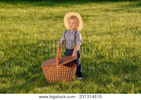 Portrait of toddler child outdoors. Rural scene with one year old baby boy wearing straw hat and picnic basket