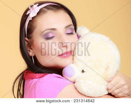 Portrait Of Childish Young Woman With Headband Holding Toy. Infantile Girl In Pink Hugging Teddy Bea