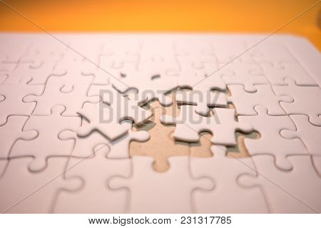 Business Background White Jigsaw Placed On Orange Table With Copy Space. Image For Texture, Problem,