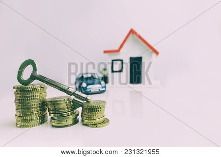 Key On Top Of A Stack Of Coins With A Blurred House And Car On The Background: Real Estate, Property