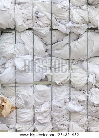 Big Metal Basket Container With Hotel Dirty Laundry Beddings And White Fabric Texture Background