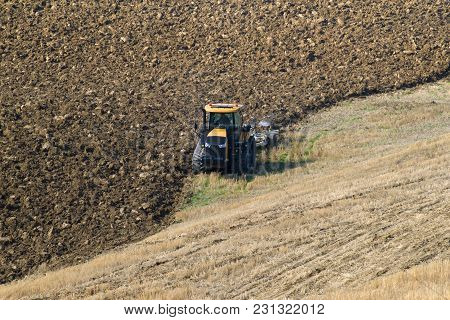 Tuscany, Italy - September 23, 2017: A Crawler Tractor Is Working On Plowing A Field On A September