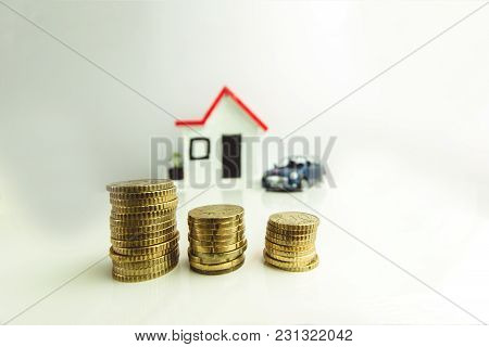 Coins Stacked With A Blurred House And Car On The Background: Real Estate, Property Investment, Hous