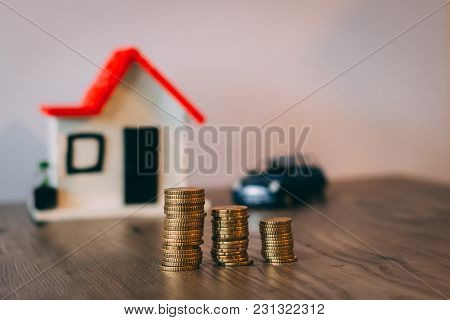 Coins Stacked On Top Of A Wooden Table, With A Blurred House And Car On The Background: Real Estate,