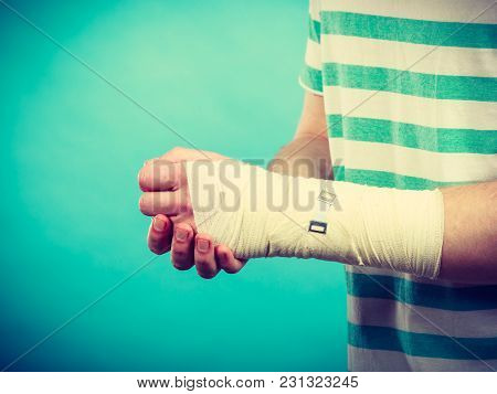 Pain And Injury Concept. Young Man Holds Bandaged Hand. Injured Part Of Body. Medicine And Healthcar