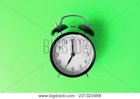 Vintage Black Alarm Clock On Green Color Background