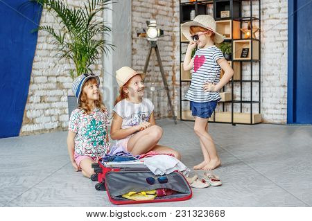 Happy Children Are Going On A Trip. Girls Try Clothes. Concept Tourism, Trip, Vacation, Rest, Sea