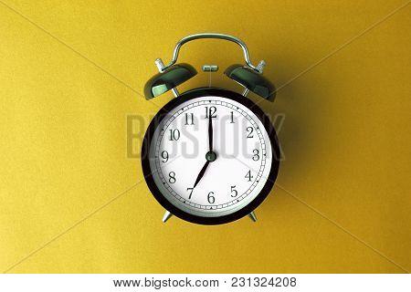 Vintage Black Alarm Clock On Yellow Color Background