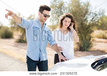 Man And Woman Standing By The Car Outdoors Missed The Road As They Are Trying To Find A Right Way Wi