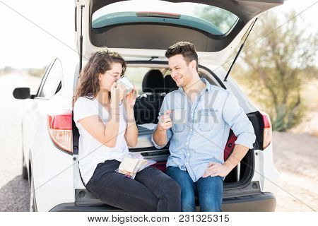 Handsome Guy Sitting In Car Trunk With His Girlfriends Drinking Coffee On Road Trip