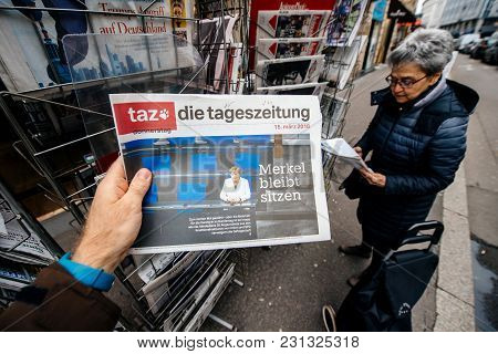 Paris, France - Mar 15, 2017: Man Reading Buying German Die Tageszeitung Newspaper At Press Kiosk Fe