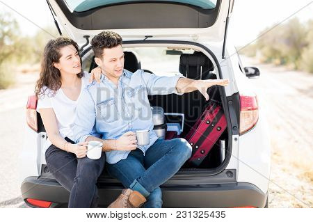 Handsome Young Man And His Girlfriend Sitting On Open Car Boot In Countryside, With Man Showing Some