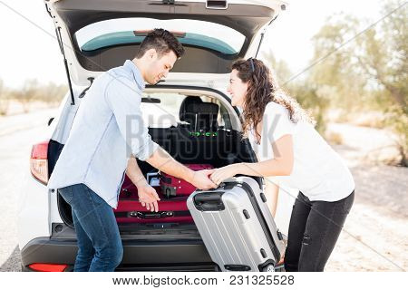 Man Helping His Girlfriend To Load A Heavy Suitcase Into Car Trunk