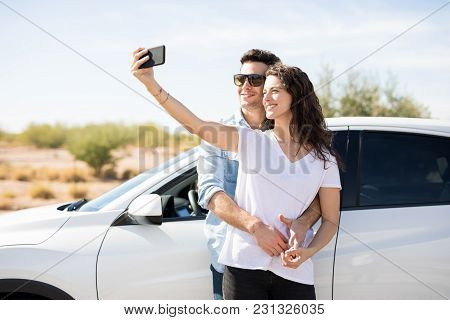 Beautiful Couple Hugging And Smiling While Standing Near A Car, With Woman Taking Selfie Using A Sma