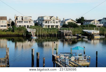 Avalon, New Jersey - July 18, 2015: Tranquil Ocean Waters In Front Of A Row Of Luxury Waterfront Sum