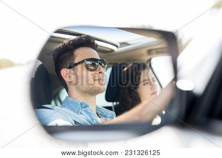 Reflection In Side View Mirror Of Young Man Driving Car With Girlfriend