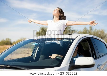 Attractive Young Woman Standing Out Of The Sunroof With Arms Outstretched  And Her Partner Driving C