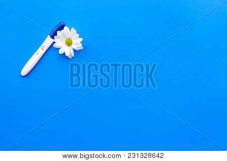 Joy Of Long-awaited Pregnancy. Pregnancy Test With Two Stripes Near Flowers On Blue Background Top V