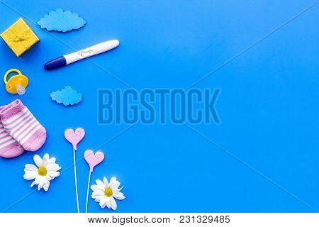 Pregnancy Test, Socks And Flowers On Blue Background Top View Mock Up