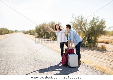 Portrait Of Caucasian Couple Hitchhiking On The Road . Man Holding Luggage And Woman Looking For Lif
