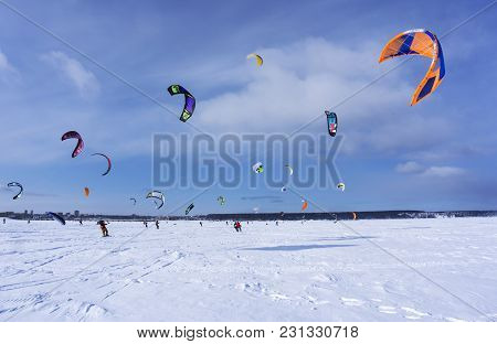 Perm, Russia - March 09, 2018: Snowkiters Compete In A Race On The Ice Of A Frozen Lake In The Backg