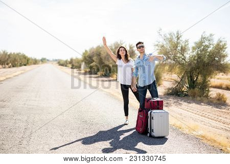 Tourist Couple Standing On Road With Luggage Hitchhiking And Hailing For Lift In Countryside