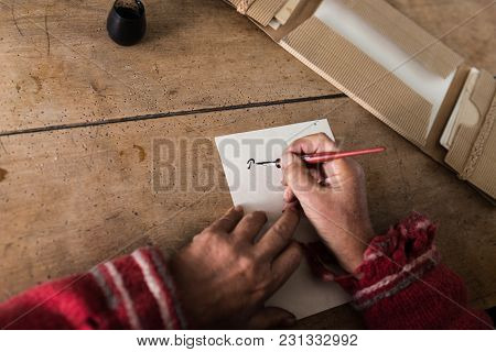 Hands Of A Senior Man Doing Calligraphy Writing On A Sheet Of White Paper Using An Old-fashioned Nib